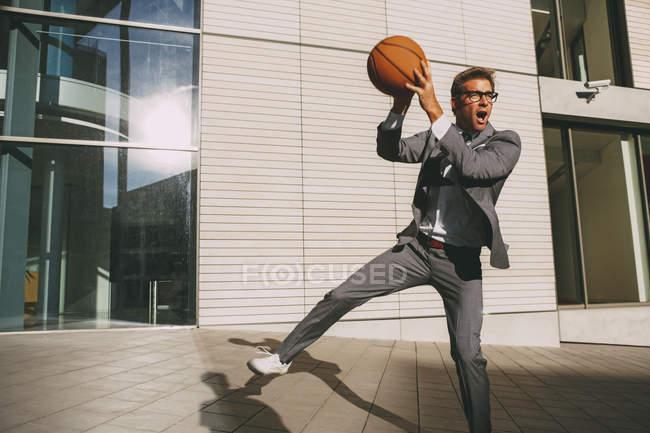 Businessman playing basketball — Stock Photo