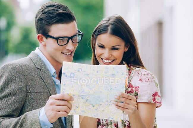 Улыбающаяся молодая пара читает карту — стоковое фото