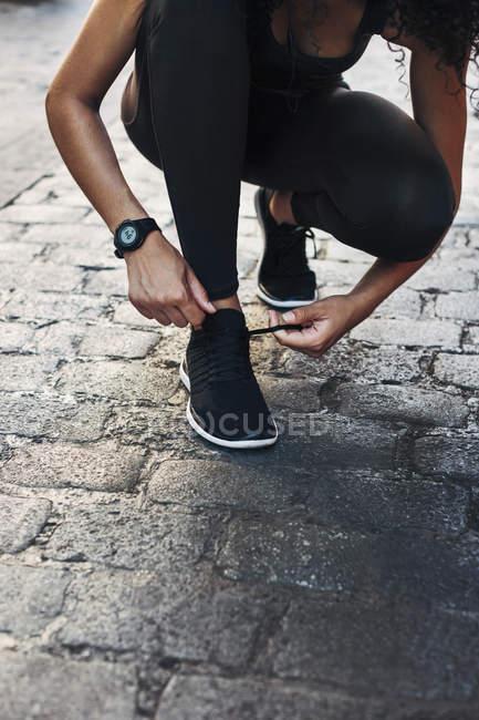 Woman tying shoe on pavement — Stock Photo