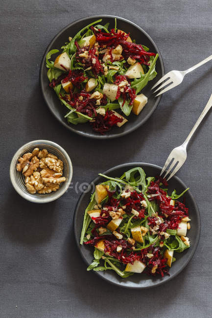Two bowls of beetroot salad with rocket and walnuts — Stock Photo