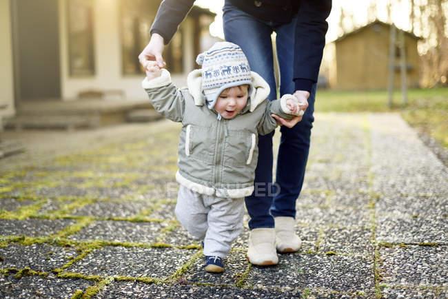 Babymädchen mit Hilfe ihrer Mutter laufen lernen — Stockfoto