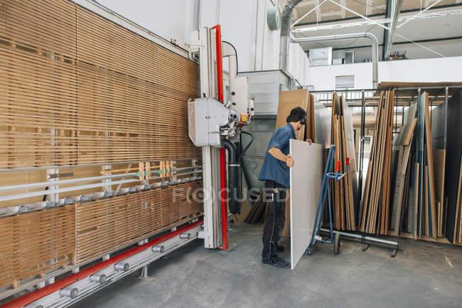 Menuisier en tenant la planche de bois du magasin — Photo de stock