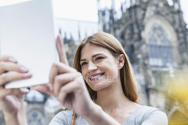 Germany, Cologne, portrait of smiling young woman taking a selfie in front of Cologne Cathedral — Stock Photo