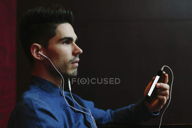 Profile of young man hearing music with earphones in front of black background — Stock Photo