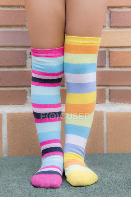 Feet of a girl with different striped colored socks — Stock Photo