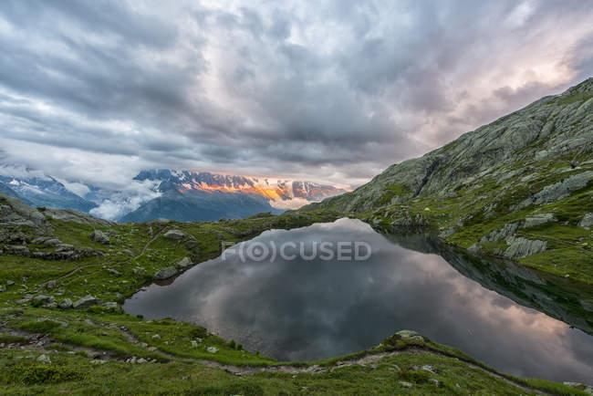 France, Mont Blanc, Lac Cheserys, Mont Blanc reflété dans le lac par une journée orageuse au coucher du soleil — Photo de stock