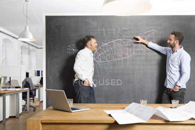Deux hommes d'affaires, discutant dessin au tableau noir — Photo de stock