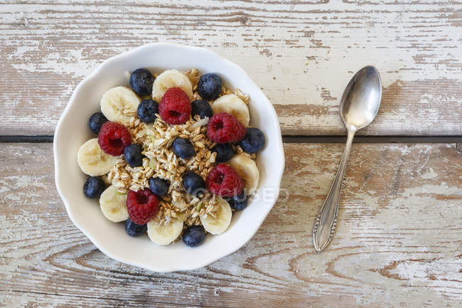 Bowl of muesli with banana slices, raspberries and blueberries — Stock Photo