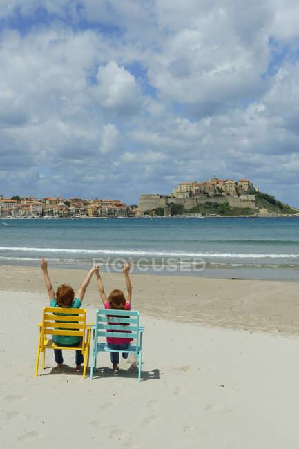 Korsika, Calvi, zwei Kinder sitzen in Liegestühlen am Meer — Stockfoto