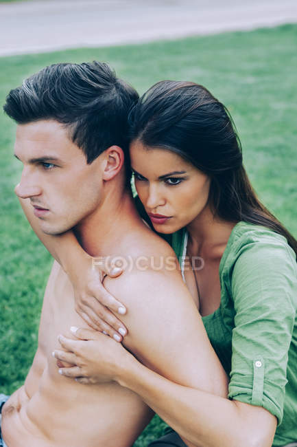 Affectionate young couple lying  in a park — Stock Photo