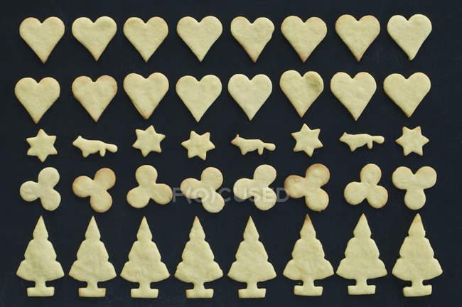 Vista superior de diferentes galletas en la superficie negra - foto de stock