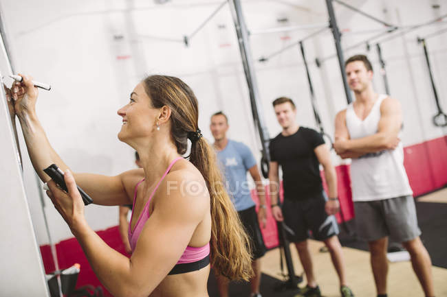 CrossFit тренер написания упражнений на доске — стоковое фото