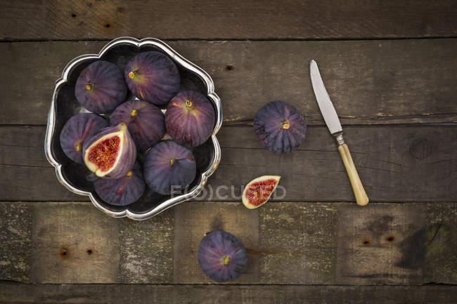 Taça de figos e uma faca em madeira escura — Fotografia de Stock