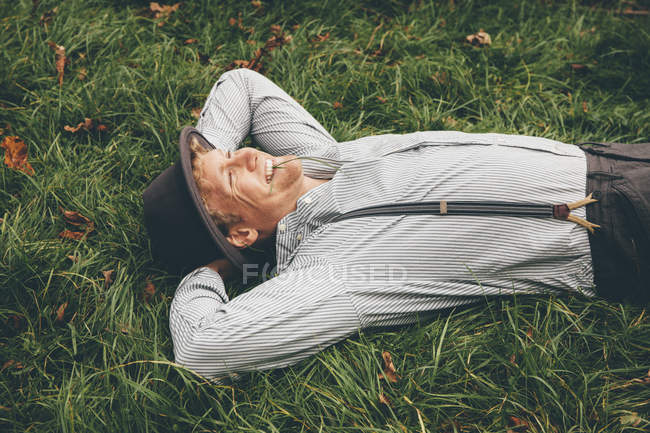 Smiling young man lying on a meadow with hands behind his head — Stock Photo
