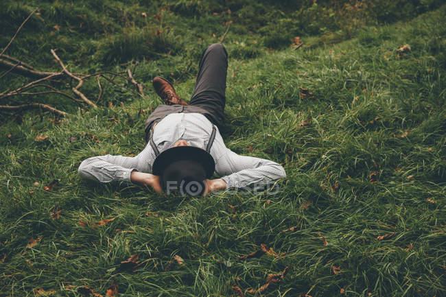Молода людина лежала на луг з руки за голову — стокове фото