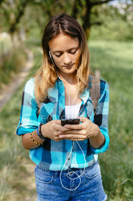 Teenage girl with smartphone and earphones — Stock Photo