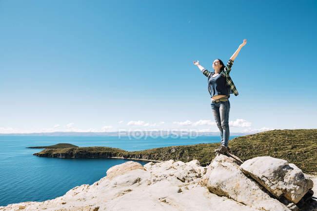 Mujer feliz de Bolivia, Departamento de La Paz, con los brazos levantados sobre la Isla del sol lago Titicaca - foto de stock