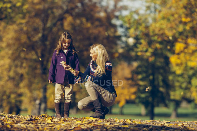Mother and daughter playing with dry leaves in autumnal park — Stock Photo