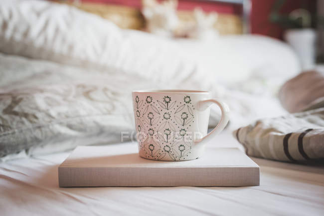 Book and cup of coffee on a bed — Stock Photo