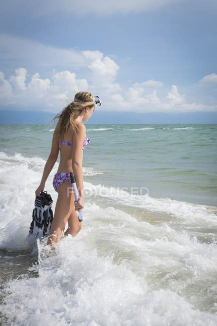 Mexico, Nayarit, teenage girl with snorkel and fins walking into the sea — Stock Photo