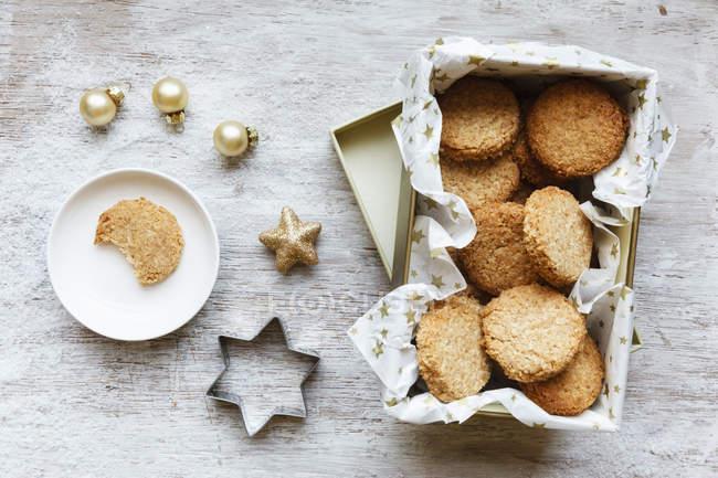 Caja de galletas de grano entero cocos, decoración de la Navidad y cortador de la galleta en la madera - foto de stock