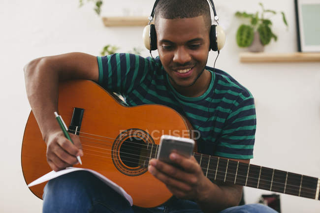 Man with guitar using smartphone — Stock Photo