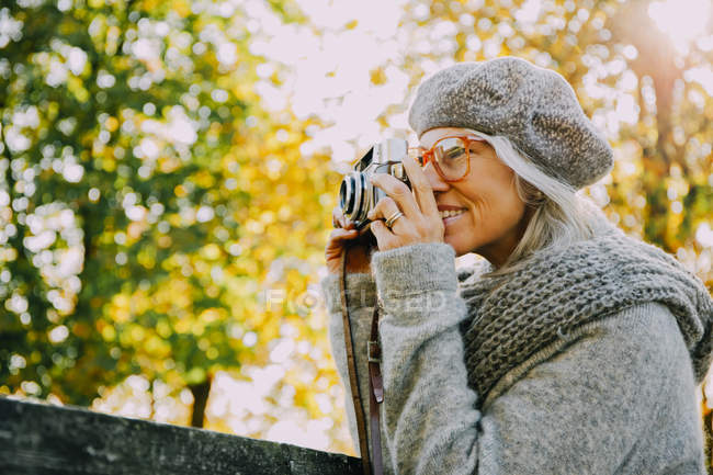 Woman taking pictures with an old camera in an autumnal park — Stock Photo