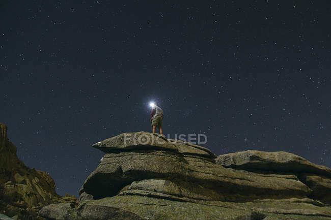 España, hombre con faro bajo un cielo estrellado sobre una roca en La Pedriza - foto de stock