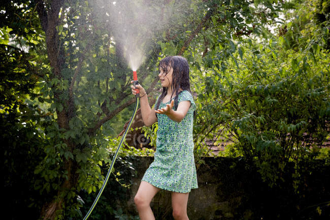 Girl cooling herself with garden hose — Stock Photo