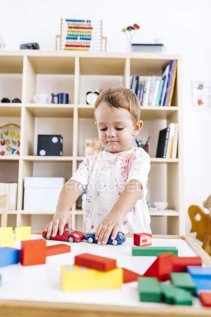Portrait de petit garçon jouant avec des voitures jouets — Photo de stock