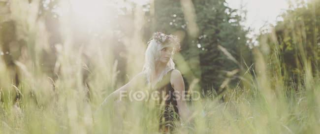 Девушка с цветами в волосах на закате — стоковое фото