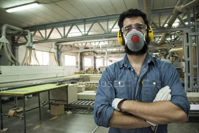Man with hearing protection, mask, safety glasses and gloves with his arms crossed in a factory — Stock Photo