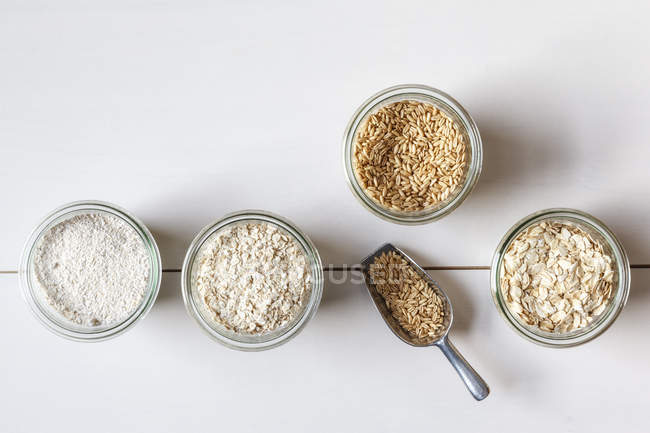 Glasses of oat grains, flakes and bran on white surface — Stock Photo