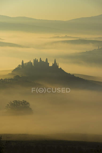 Italy, Tuscany, San Quirico d'Orcia, view to rolling landscape at sunrise in the fog — Stock Photo