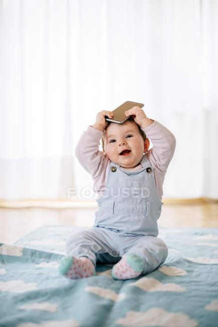 Retrato de menina sentada no cobertor segurando smartphone na cabeça — Fotografia de Stock