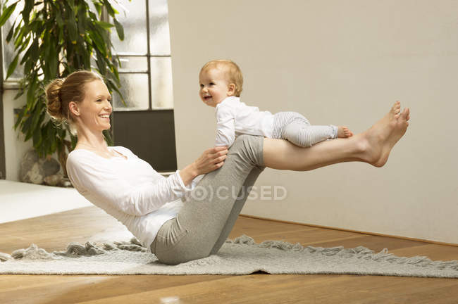 Woman balancing baby on her legs — Stock Photo