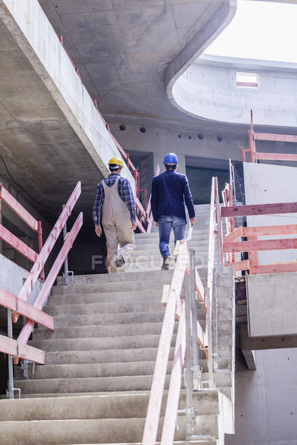 Construction worker and architect on construction site walking upstairs — Stock Photo