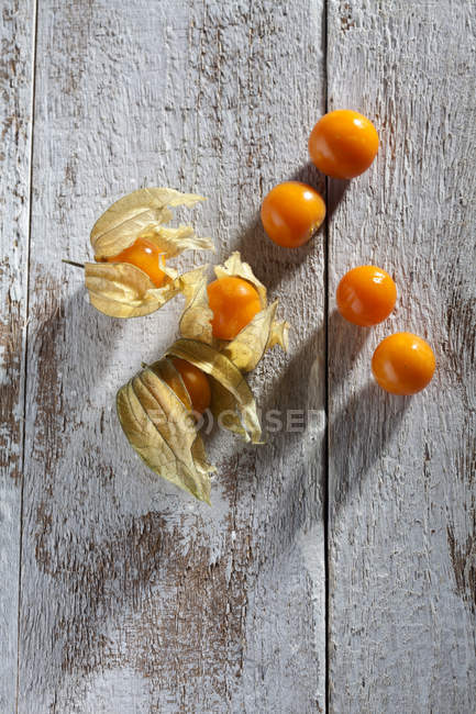 Physalis with dried flowers on shabby wooden surface — Stock Photo