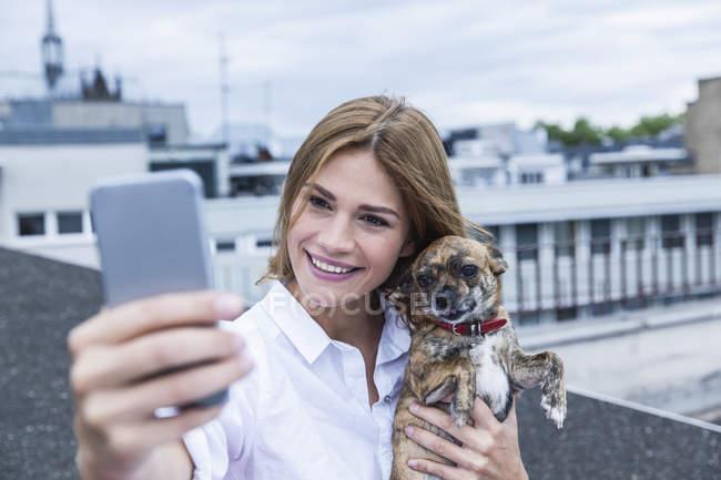 Portrait de la souriante jeune femme prenant un selfie avec son chien sur le toit-terrasse — Photo de stock