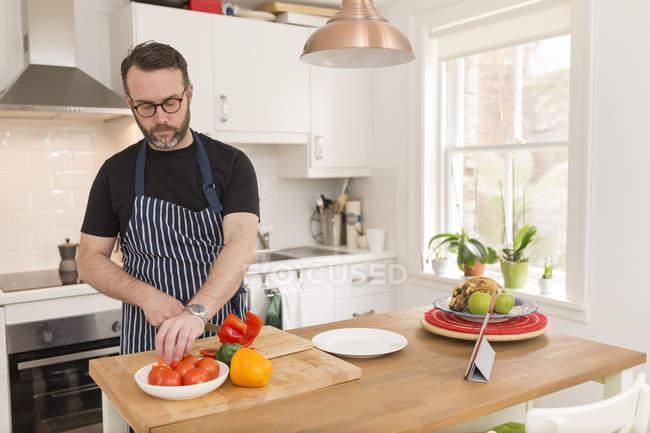 Homem preparando legumes na cozinha — Fotografia de Stock