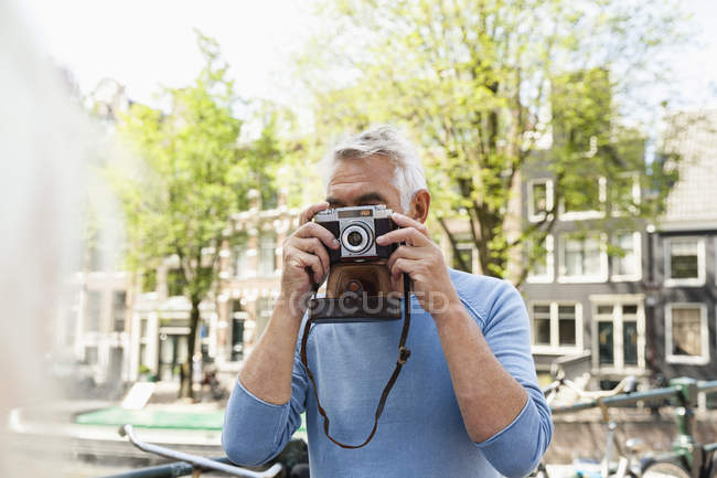 Netherlands, Amsterdam, senior man taking a picture with analog camera — Stock Photo