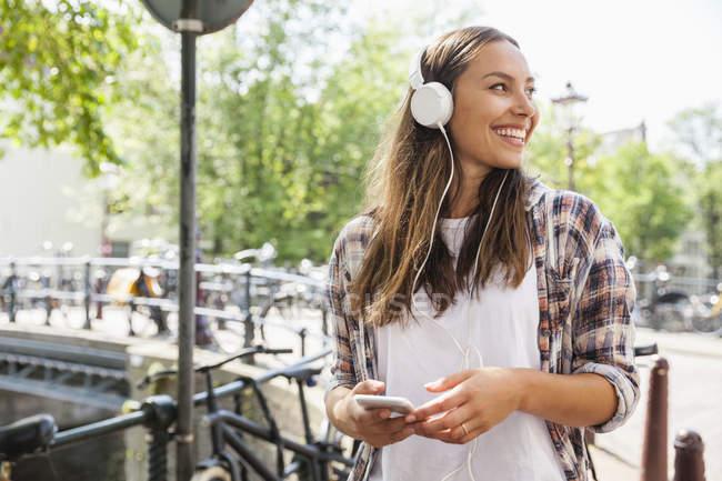 Pays-Bas, Amsterdam, jeune femme heureuse avec écouteurs — Photo de stock