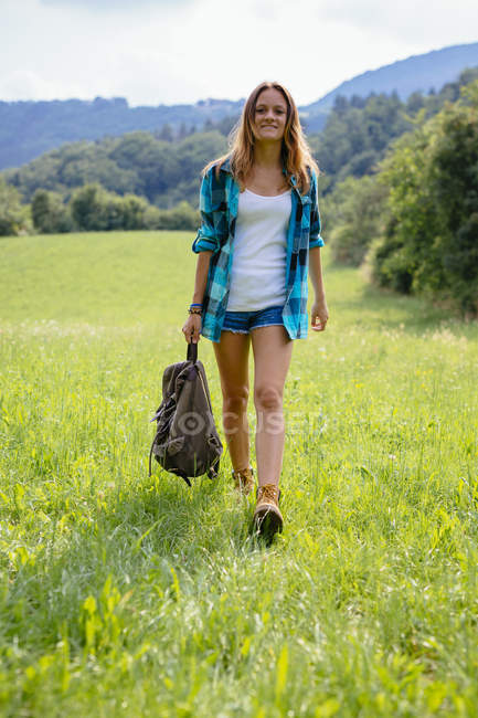 Alto Adige,  teenage girl with backpack walking on a meadow — Stock Photo