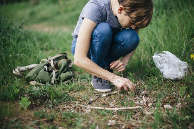 Junge Frau kauert auf einer Wiese und blickt nach unten — Stockfoto