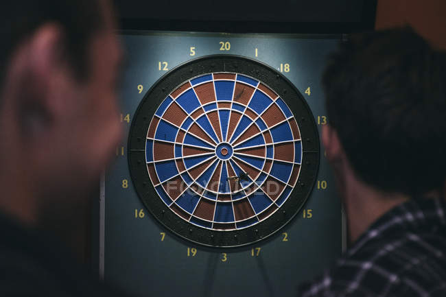 Rear view of two men playing darts — Stock Photo