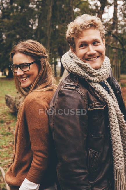 Пара, стоящая спиной к спине в парке — стоковое фото