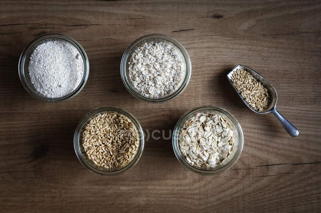 Glasses of oat grains, flakes and bran on dark wood — Stock Photo