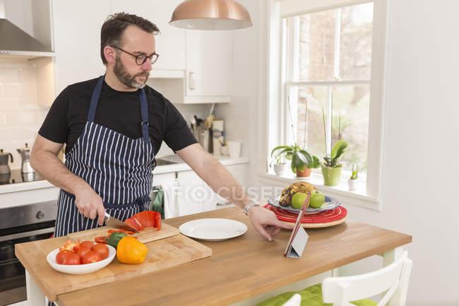 Homem usando tablet digital na cozinha enquanto prepara legumes — Fotografia de Stock