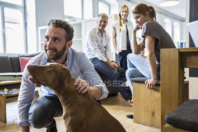 Happy colleagues with dog in modern office — Stock Photo