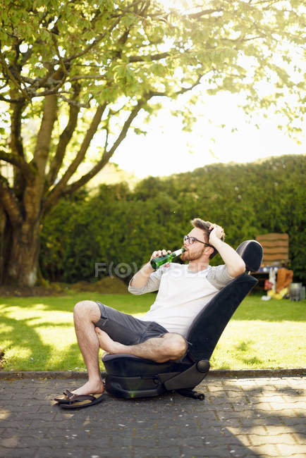Young man sitting on removed car seat drinking beer — Stock Photo